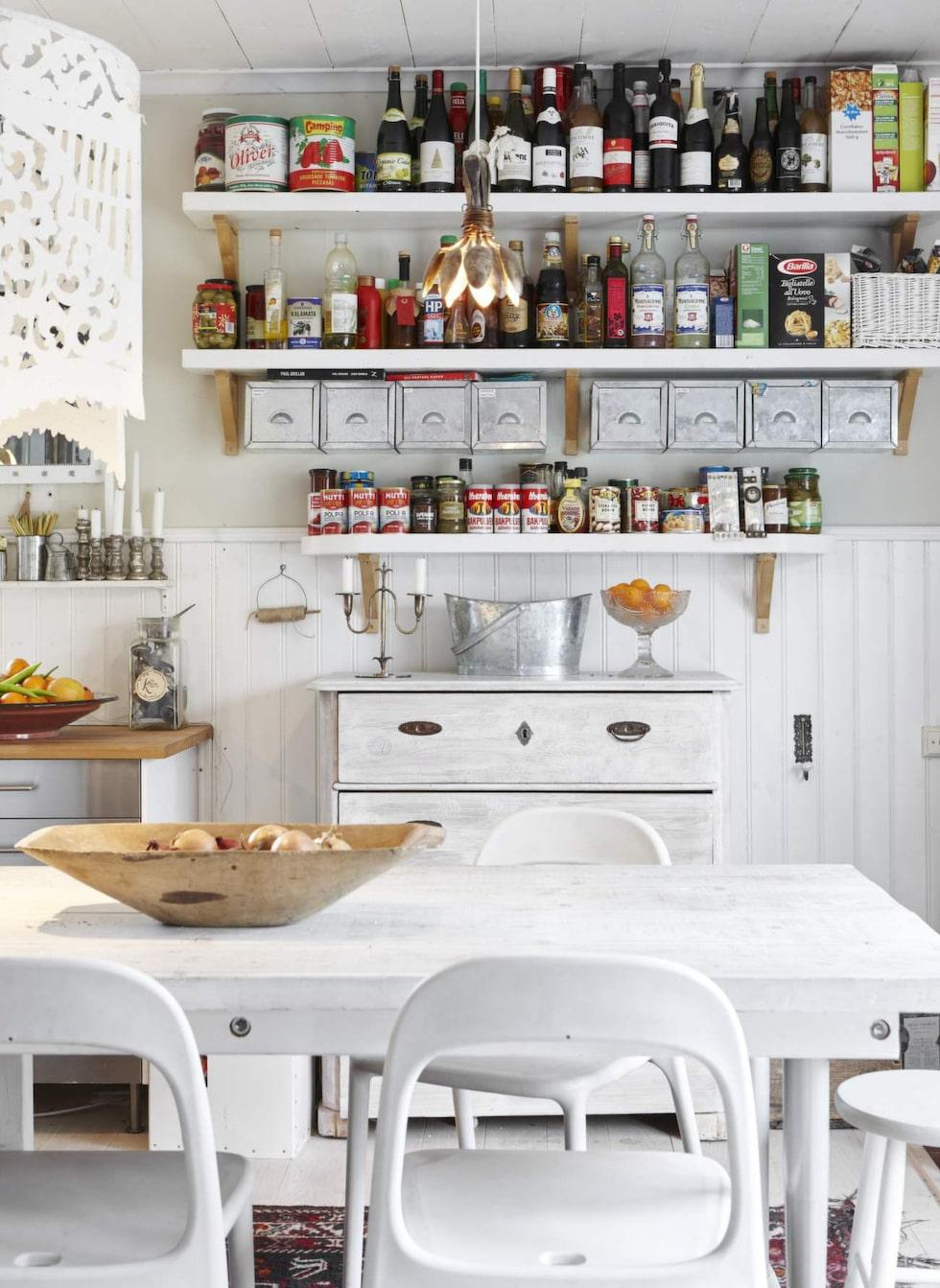 Till det rustika matbordet på tre meter som René byggt gjorde han även hyllor till köket av samma brädor. Här står det mesta som används dagligen.