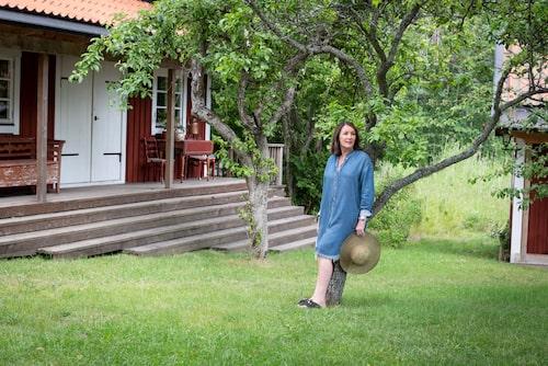 Catherine framför ett av gästhusen, den så kallade Farfarsstugan. Runt huvudhuset finns flera andra byggnader som i dag fungerar som gästhus och förråd.
