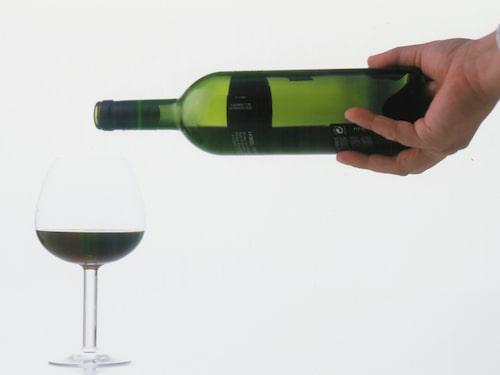En vinkypare eller sommelier greppar med hela handen runt flaskans botten.