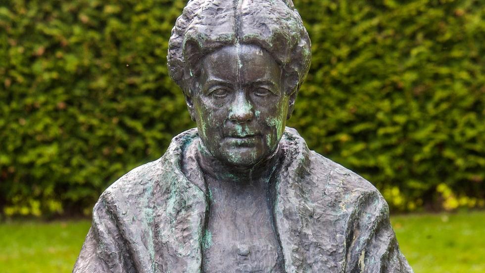 Selma Lagerlöf sitter staty på en tron i Rottneros skulpturpark.