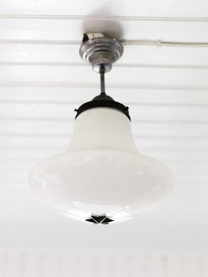 Antik. Den gamla lampan med de svarta järndetaljerna är ett auktionsfynd och den passar perfekt i badrummet.