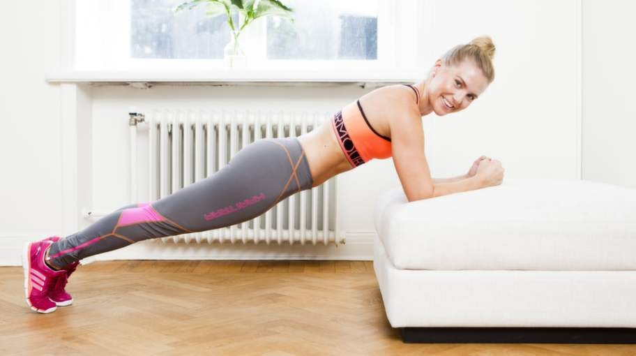 Planka i soffan med två sorters fothopp.Fokus: Styrka för bålen, axlar och vader samt kondition.Så gör du:1    Ställ dig i en rak plankposition med under- armarna i soffa eller fåtölj. Sug upp naveln mot ryggen och sträva efter sänkt höft i ett sträckt läge.