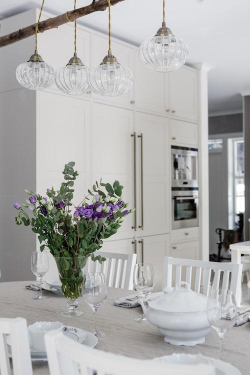 Över matbordet hänger en kreativ lamplösning som Pernilla skapat av en gren från ett träd på tomten och fönsterlampor från Ellos.
