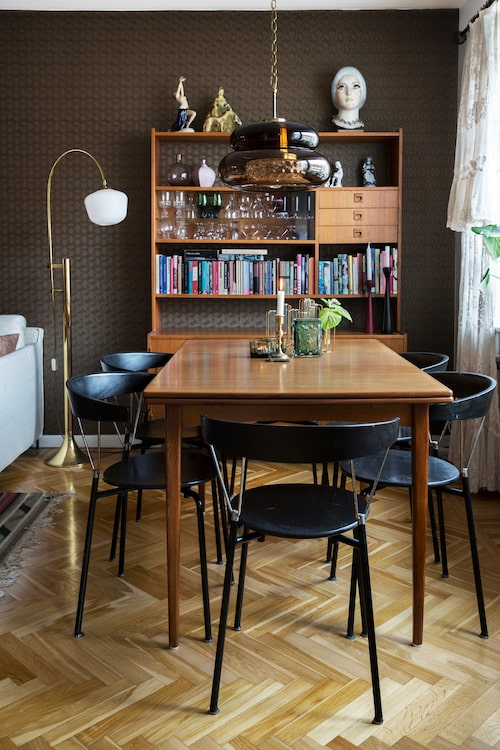Teakbordet kan dras ut och rymma 15 matgäster under 70-talslampan från Orrefors. De nätta karmstolarna med kromdetaljer är oväntat sköna att sitta i, ett absolut krav från ägarinnan.