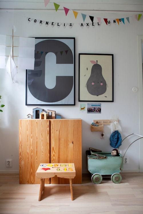 Grafiskt och naturmaterial i yngste sonen Cornelis rum. Skåp Ivar från Ikea, trähus från Kids concept och segelbåt i taket från Haptic lab. Poster Pirum parum från Fine little day och poster med C från Playtype.