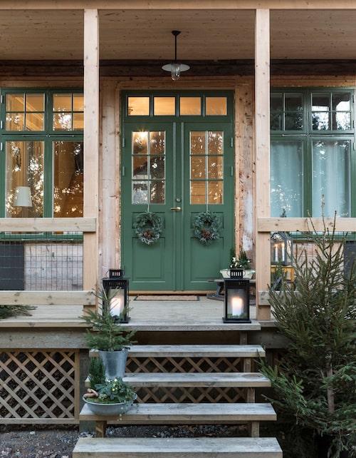 Entrén väntar på brädfodring, men funkar fint som det är, då de råa väggarna passar fint ihop med de gröna snickerierna. Ljuslyktor, Ikea. Kransarna har Linda gjort själv. Dörr och fönster är målade i linoljefärg i nyansen Grön 2:4, Wibo färg.