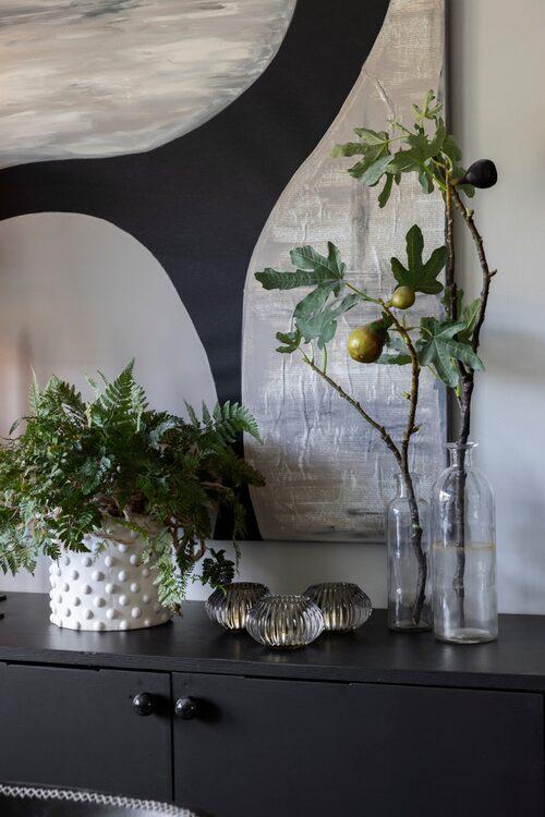 Här samsas en ormbunke i kruka med en fikonkvist framför Annas egenhändigt målade konstverk. Kruka, Silkflower. Ljuslyktor, Dollarstore.