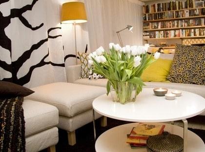 Dolda rör. Alla fula rör på ena långväggen doldes bakom ett draperi. På det gjorde inredarna en trädapplikation av tyget Ditte på gardinen Vivan, Ikea. Ett rejält soffbord, Imfors, Ikea, med hylla under är också praktiskt.