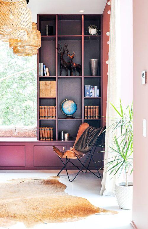 Den platsbyggda hyllan med en sittbänk vid fönstret i biblioteket är byggd av Emelies mammas man och sedan målad i kulören Bordeaux, från Jotun.