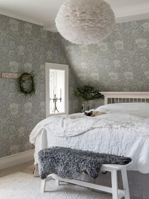 Katten Ärtus tar en tupplur i parets sovrum. Sänggaveln har Therese och Johan ritat. Till väggarna har de valt tapeten Honeysuckle and tulip från William Morris.