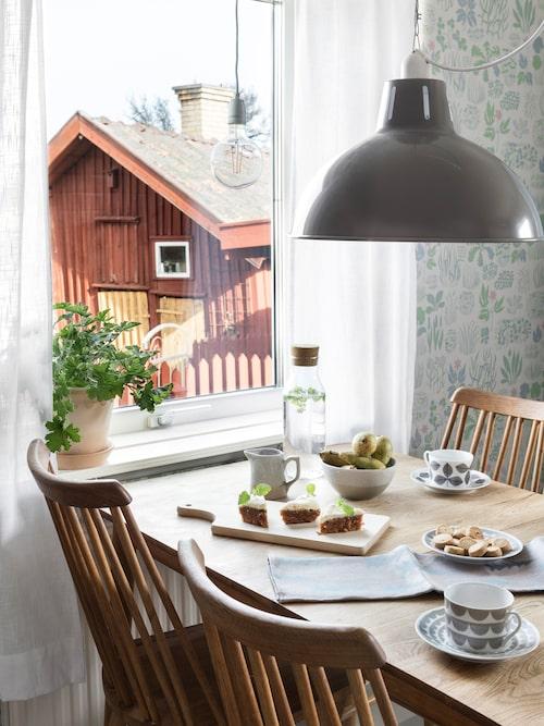 """Från köksfönstret har man fin utsikt över det gamla charmiga kvarteret med faluröda bodar och den gamla """"slaskegatan"""". Lampa, Granit. Koppar och fat House of Rym. Skärbräda, skål, mjölkkanna, Strömshaga."""