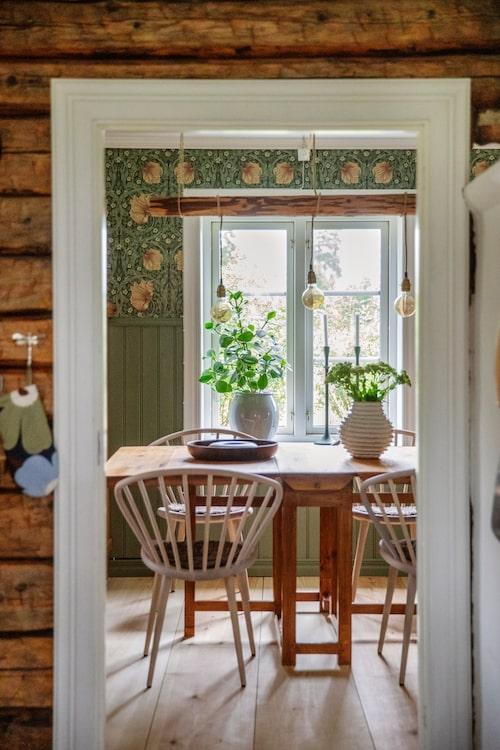 """Runt ett gammalt fällbord i matsalen står stolar Holly från Stolab. Tapet """"Pimpernel"""", William Morris."""