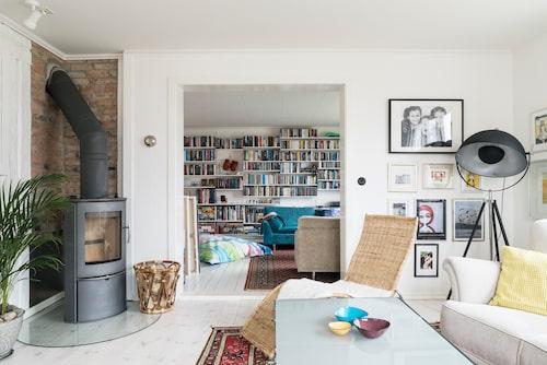 Från vardagsrummet ser man in i biblioteket. Kamin, från Lotus. Vedkorg, Jassa, Ikea. soffbord, Moment, Ikea. Golvlampa, Dome, Malmbergs.