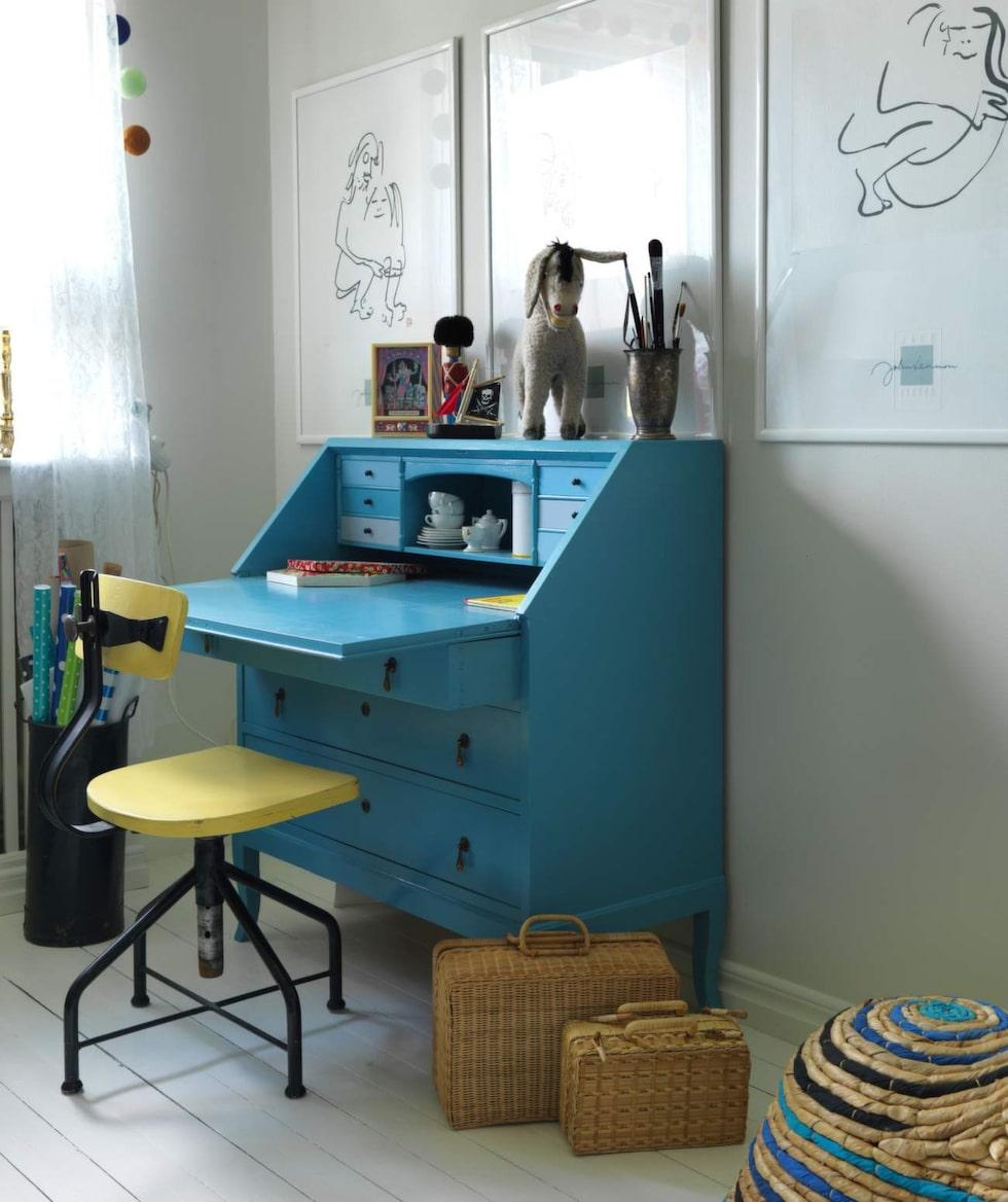 Skrivplats i gult och blått. Sekretären är ett arvegods som målats om. Stol från en auktion utanför Lin- köping, korgväskor från Italien.