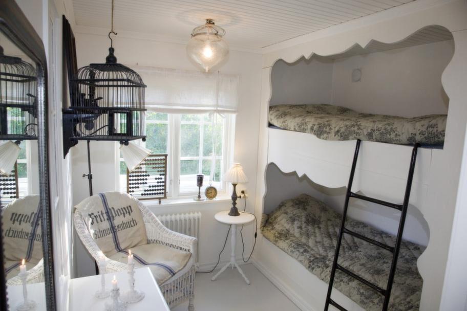Mysigt. Hemsnickrade våningssängar i lillstugan med gammaldags täcken passar<br>utmärkt för ett litet rum.