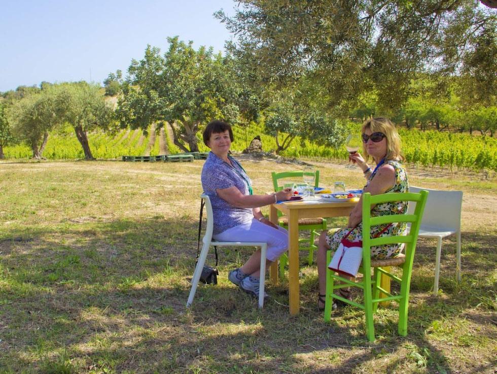 På siciliansk vingård. Britt-Inger Johansson och Elisabet Isaksson från Växjö njuter av den goda maten och drycken under ett olivträd på vingården Buonivini.