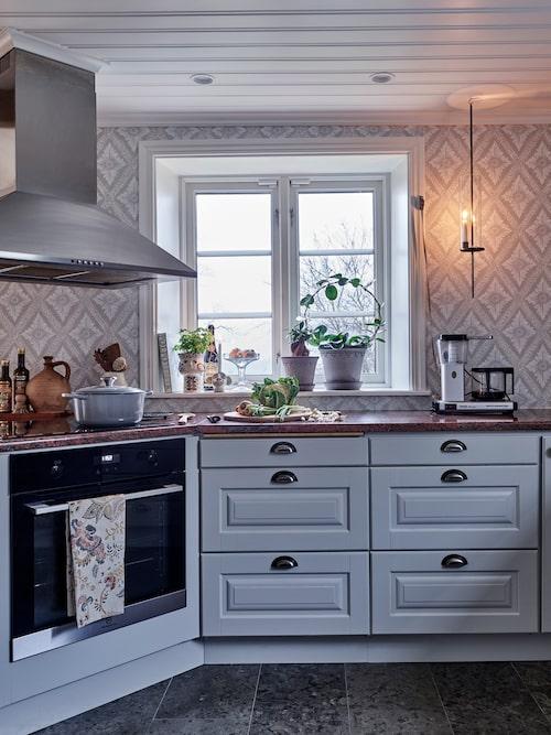 Köket var i fint skick när Sandra och Andreas köpte huset, så här har de bara lackerat om luckorna och bytt handtag och vitvaror. Krukor, Bergs Potter. Ljuslykta, Grafitgrå. Golv av öländsk kalksten, Naturstenskompaniet. Köksluckorna är målade i kulören 2502-Y.