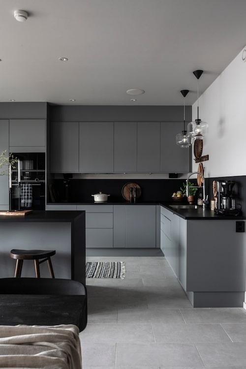 Köket är stilrent i grått, svart och vitt. Bänkskivan i svart laminat fortsätter upp på väggen som stänkskydd och förstärker kökets karaktär. Mellangrå kök, Arkitekt Plus, Marbodal. Barstolar, Ellos. Lampor över diskbänken, Globen Lighting. Matta, Ikea.