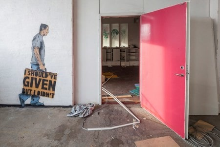 """""""I shoud've given but I didn't"""" (Jag skulle ha gett men gjorde inte det) står det på skylten som mannen på väggmålningen bär, på väg in genom den rosa dörren."""