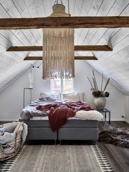 Även innertaket i Annas sovrum på övre plan fick stryka på foten. Nu finns här i stället frilagda takbjälkar och en härlig takhöjd. Taklampa, Blommingville. Korg, Ikea. Matta och fårskinn, Madame Plantier.