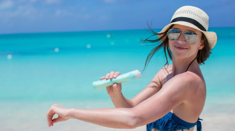 smiling young woman applying sun cream on tropical beach