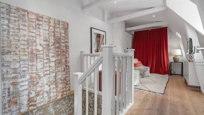 Trappan upp till andra plan. Bakom röda draperiet finns den uppfällbara sängen.