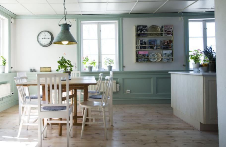 """Pastellfint. Spegelpanelen och fönsterfodren i köket är målade i en pastellgrön nyans som för tankarna till Carl Larsson.<br>Matbordet är köpt på Blocket för något år sedan. Fia """"tvingade"""" sin man att köra 10 mil enkel väg för att hämta det. Det är över 100 år gammalt och hon har väntat i över 15 år på att ett sådant skulle dyka upp."""