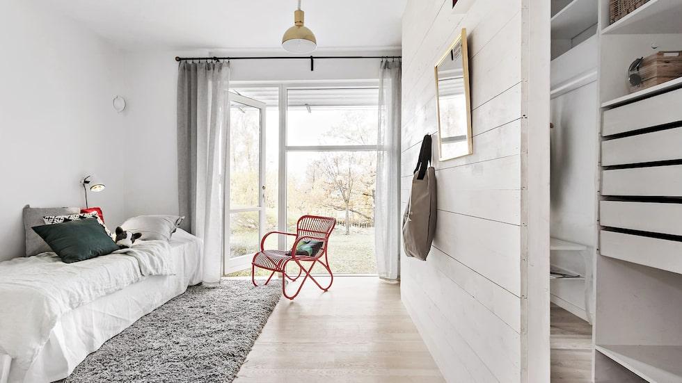 Ett av sex sovrum. Semiöppen klädkammare bakom en fin panelad vägg. Utgång till trädgård, vita väggar och ekparkett.