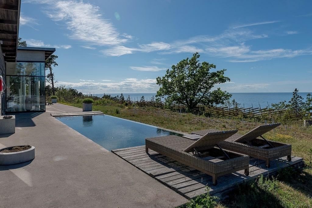 Huvudbyggnaden är ett enplanshus med stora glasfönster mot havet, och runtom hela löper en gjuten terrass på 190 kvadratmeter med en integrerad infinity-pool på havssidan.