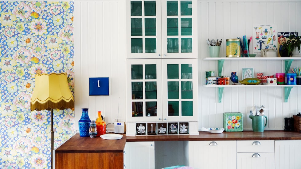 Köket var renoverat när Katja och Björn flyttade in och köksinredningen i radhuset kommer från Ikea. Vitrinskåpet och de öppna hyllorna är fulla av retrofynd och ärvda pryttlar.Gröna detaljer, färgglatt porslin och plåtburkar är fyndade på loppis. Den gröna kannan kommer från Ikeas Ilse Crawford-kollektion. Skålen på bänken är Picknick för Rörstrand.