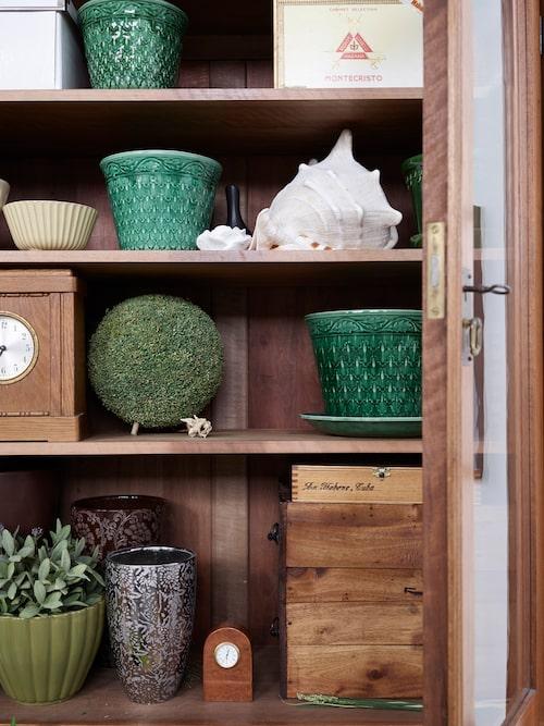 Skåpet är fyllt med vackra ting, så som de gröna hundraåriga ekollonkrukorna från Gustavsberg.