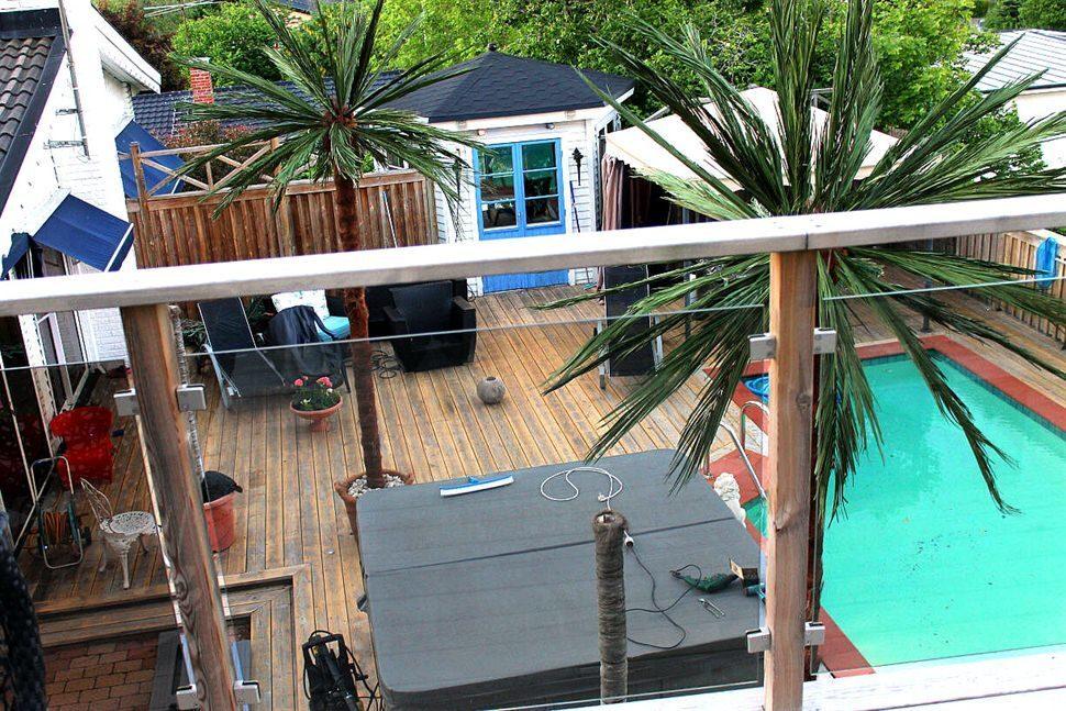 Vy från gästhusets terrass: man ser poolen, jacuzzin och lusthuset/orangeriet.