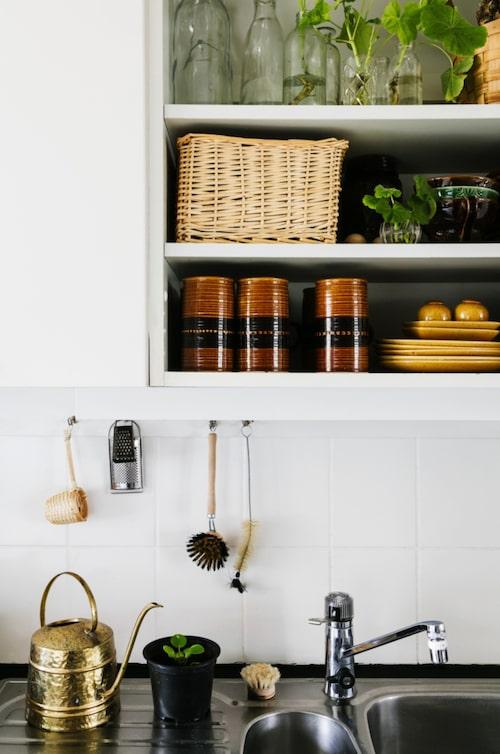 Öppna hyllor. Hyllorna i köket rymmer allehanda ting som kan vara praktiska att ha framme. Servisen kommer från Deco i Helsingborg. Vattenkannan i mässing kommer Malins föräldrahem.