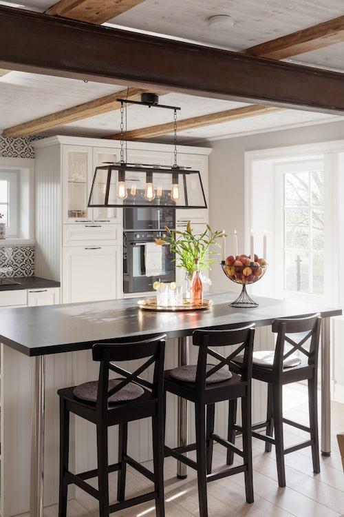 Takbjälkarna i köket är frilagda. Lampa från Rusta. Stolarna har fyndats på Blocket och målats om.