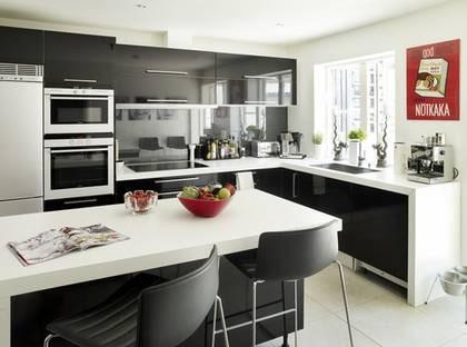 Svartvitt kök. Högblanka svarta luckor med stilrena rostfria handtag kontrasterar fint mot de vita väggarna, det ljusbeige klinkergolvet, och bänkskivorna i vitt laminat.