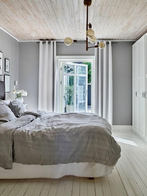 Sovrummet är inrett i en grå nyans. Från sovrummet kommer man ut till den härliga terrassen. Lampan i taket har Nicklas gjort.