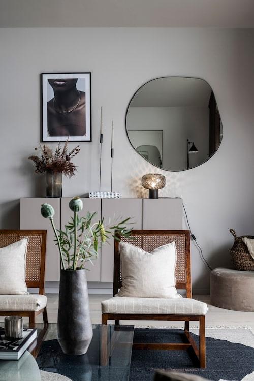 Skåpen i vardagsrummet är målade i en något mörkare kulör än väggen, NCS S4005-Y50R. Skåp, Ikea. Spegel och lampa från Zara Home. Tavla, Desenio. Vas, H&M Home. Ljusstakar, Ernst.