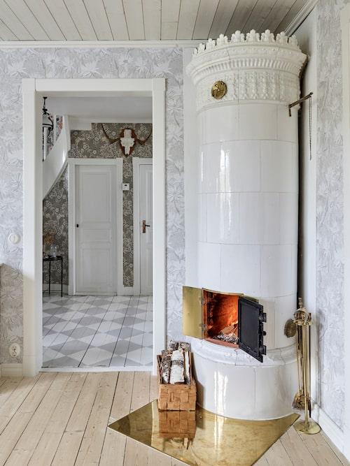 Från vardagsrummet har man en fin vy ut i hallen där Åse målat golvet i grå och vita rutor. Kakelugnen är gammal men renoverad och nyuppsatt. Eldstället i mässing är ett loppisfynd.