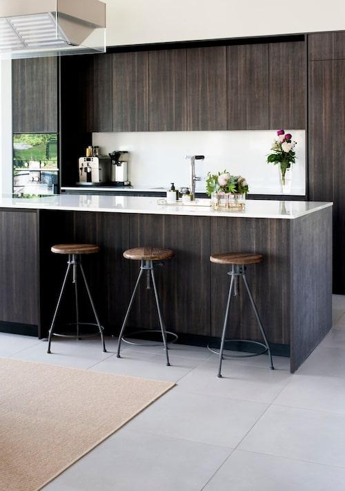 Familjens platsbyggda kök har integrerade vitvaror. Vitvaror, Gaggenau. Barstolar, Artwood. Stengolv, Salvatori. Kök Varenna, Poliform.