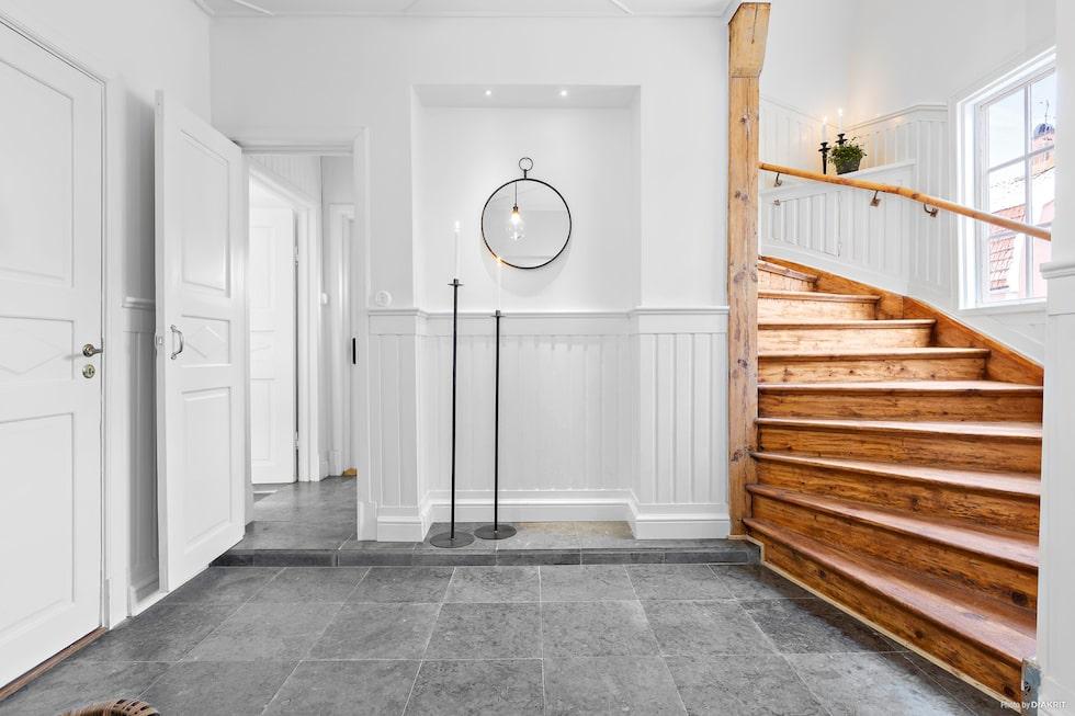Hallen är välkomnande och ljus. Härifrån nås den vackra trappan som  leder till övervåningen. Väggarna är vita och på golvet ligger  gråmelerad Kinnekullekalksten med golvvärme.