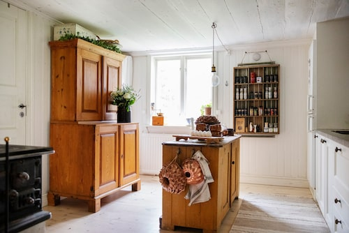 """I mitten av köket står en gammal skänk som får tjäna som köksö. Skåpet till vänster är köpt i en antikaffär och passade precis. """"Det var jättesvårt att hitta ett skåp, det är väldigt lågt i tak här"""", säger Linnea."""