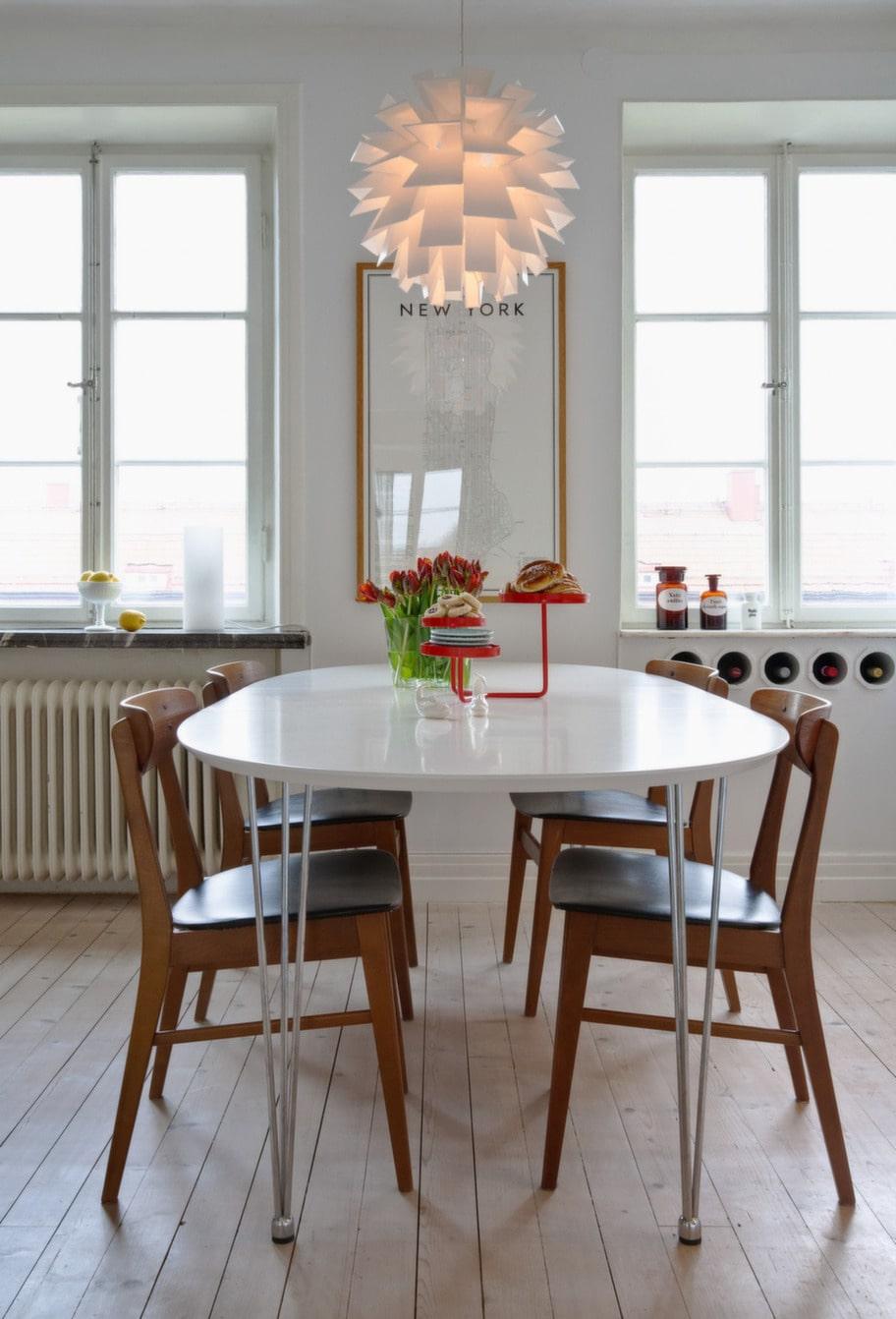"""Matbordet. Tavlan i köket heter """"2010 guide to Manhattan"""" och är gjord av David Ehrenstråle. Köksstolarna i teak med svart skinnsits från danska Farstrup hittades på loppisrunda under en semester på Österlen för två år sedan. Rött kakfat Cookie från Asplund, design Stina Sandwall. Under fönstren till höger finns ett inbyggt vinställ."""