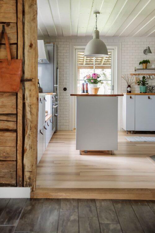Det ljusa köket har kakel på väggarna. Köksinredning, Ikea. Lampa, Granit.