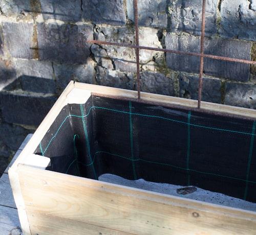 Täck botten och insidan med markväv och häfta fast den högst upp.