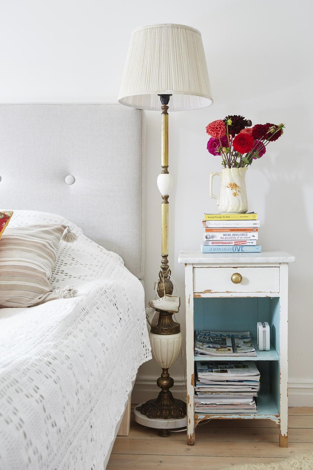 Sängbord med vacker patina och sanslöst vacker vintage golvlampa, båda loppisfynd. Dahlior i starka färger, en av Hannas favorit bland blommor.