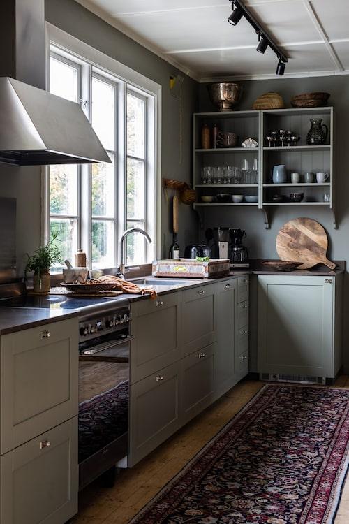 Köket går i en grågrön färgskala där såväl väggar som kök är målade i samma kulör, NCS 4005-G80Y. Köket kommer från Ikea och bänkskivan från Silestone. I taket sitter en spotlightskena från Xcen.