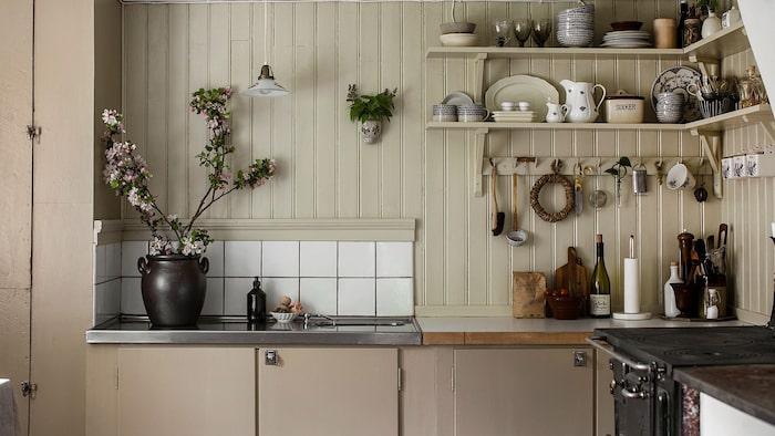 I köket är det målad pärlspont och vägghyllor för förvaring.