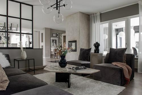 Vardagsrummet är elegant och inbjudande med den stora avdelande väggen av träreglar som Josefin och Lenny byggt själva. Svart skulptur, rund svart vas, kuddar, svart kruka och silvriga ljusstakar, från Mio. Väggskåp, Bestå, från Ikea. Piedestalen har Josefin gjort själv.