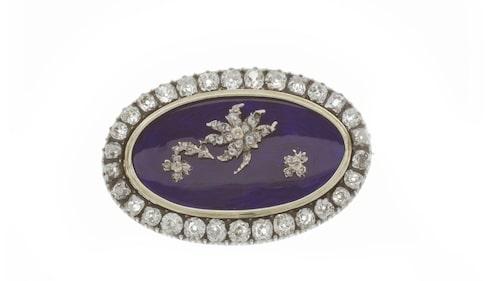 Brosch, 29 500 kronor. Tillverkad på 1800-talet i silver och 14 karats rödguld. Den är utsmyckad med slipade diamaner och rosenstenar på totalt 3 carat. På framsidan sitter blå emalj.