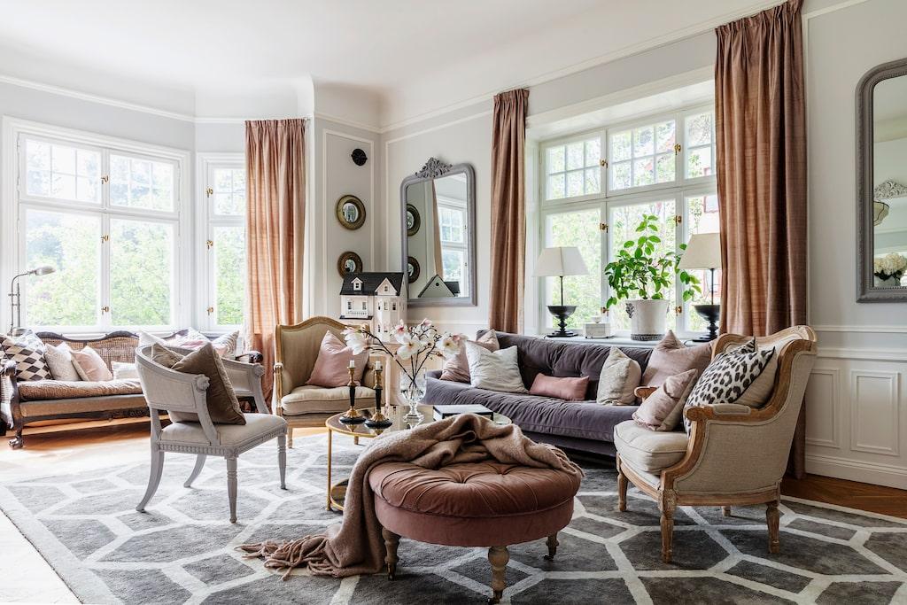 Familjens vardagsrum har många inbjudande sittplatser. Rummet är smakfullt möblerat för att plocka fram det bästa i huset. De ateljésydda gardinerna av dupionsiden ramar vackert in fönstren. Pall, Två Sekler. Baljfåtölj, Epok Möbler. Bergére, Frejas Boning. Sammetsoffa, MeliMeli. Soffa i burspråk, auktion. Matta, Layered. Spegel, PR Home.